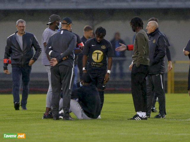 L'image de la soirée: Ndiaye, assis sur la pelouse, manifeste son mécontentement. Namur demande 2 000€ pour le libérer.
